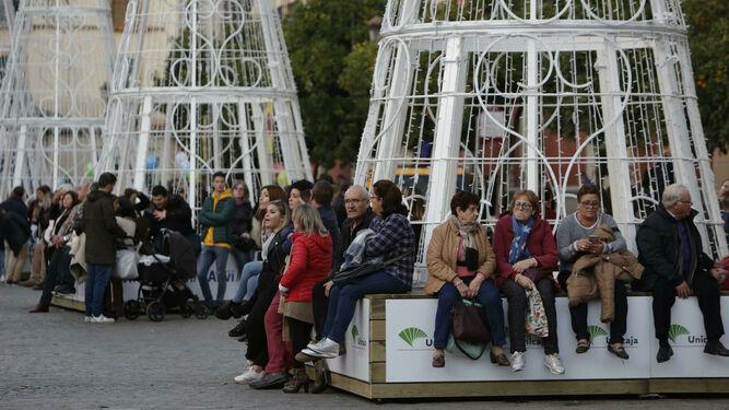 Personas esperan sentadas a que comience el espectáculo de la Plaza de San Francisco.
